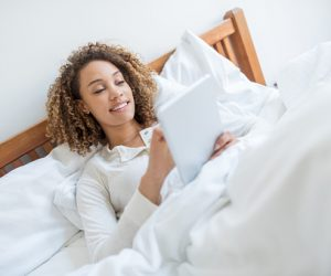 Woman reading in bed on a tablet